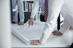Two architects discussing over a blueprint in the office, mid section Stock Images