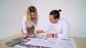 Two Architects Discussing Plan Together At Desk With Blueprints. 4 k stock video footage
