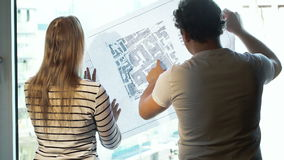 Two architects discussing a project looking at the. Man and woman architects standing by the window and talking about city construction looking at schematic map stock footage