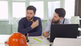 Two architects gesture at the table stock footage