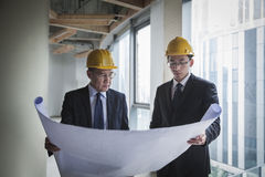Two architects in hardhats examining a blueprint in an office building Stock Images