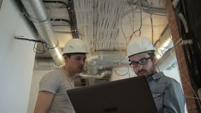 Two architects in helmets talking looking at laptop standing at construction site. Specialist holds laptop. Two architects in helmets talking looking at laptop stock video footage