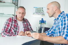 Two architects looking at blueprint working in office royalty free stock image