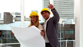 Two architects looking at blueprints. In slow motion stock video footage