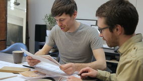 Two architects looking interior plan and talking sitting in office indoors. Man holds color images of interior that they have to implement and discuss his stock video footage