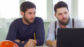 Two architects looking at laptop screen. Two young caucasian architects looking at laptop screen at the office. Bearded construction engineer in white shirt and