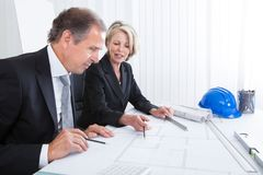 Two architects looking at plans Stock Photo