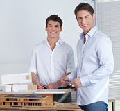 Two architects with model of house. Two happy architects in their office with model of a modern house Royalty Free Stock Photo