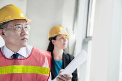 Two architects in protective workwear and hardhats working in an office building Stock Photography