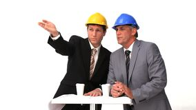 Two architects with safety helmets speaking. Against a white background stock footage