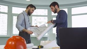 Two architects shake hands at the office. Two young male architects shaking their hands at the office. Attractive caucasian construction engineers deploying the Royalty Free Stock Photography