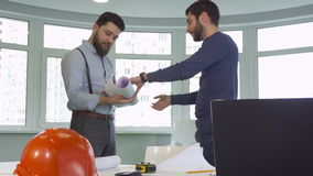 Two architects shake hands at the office. Two young male architects shaking their hands at the office. Attractive caucasian construction engineers deploying the stock footage