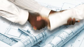 Two architects shaking hands. Agreement in architecture. Close up of two architects shaking hands against plans and blueprints background. Agreement in stock video