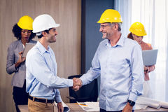 Two architects shaking hands in office Stock Images