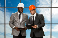 Two architects on sky background. Royalty Free Stock Photography