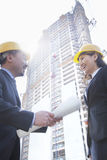 Two architects smiling at a construction site holding blueprint Stock Images