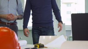 Two architects stand near the desk stock photos