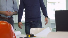 Two architects stand near the desk. Close up of two male architects standing near the desk. Construction engineers coming closer to the table with hard hat and stock video