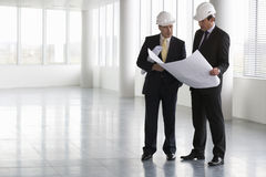 Two architects wearing hard hats looking at plans Stock Image