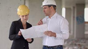 Two architects wearing protective helmet works at building site. Professional shot in 4K resolution. 104. You can use it e.g. in your commercial video stock video