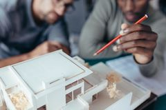 Two architects working on new construction project. Closeup of architect`s hand holding pencil pointing at architectural house model. Two male architects working Stock Photo