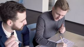 Two architects are working on the project together in their office. Male professionals are sitting at the wooden table and doing a building blueprint, using stock video