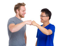 Two arm fist punch each other for caucasian and asian man Stock Photo