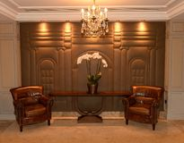 Two armchairs in luxurious hotel. Two leather armchairs in luxurious hotel either side of flowers with chandelier above Royalty Free Stock Images
