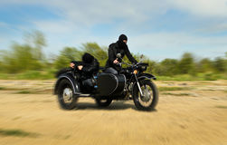 Two armed men riding a motorcycle Royalty Free Stock Image