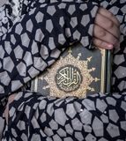 Two Arms Huging Holy Book of Quran. Two Arms of Muslim Girl Huging Holy Book of Quran royalty free stock photos