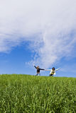 Two arms raised friends in a meadow. Two arms raised friends in a green meadow Royalty Free Stock Photography
