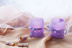 Two aromatic candles in glass candlesticks with lavender paper on table close up Royalty Free Stock Photography
