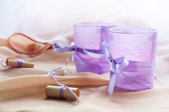 Two aromatic candles in glass candlesticks with lavender paper on table close up Royalty Free Stock Images