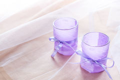 Two aromatic candles in glass candlesticks with lavender paper on table close up Stock Photos