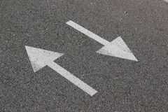 Two arrows on asphalt. Sign of two-way street Royalty Free Stock Photo