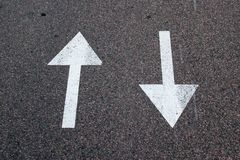 Two arrows on asphalt. Sign of two-way street. Two arrows painted on asphalt. Sign of two-way street stock photo
