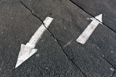 Two arrows on cracked asphalt surface. Stock Photo