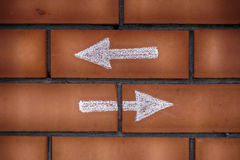 Two arrows pointing forward and backward drawn on bricks. Two different choices. Dilemma concept Stock Photos