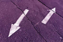 Two arrows on purple toned cracked asphalt surface. Stock Photo