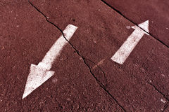 Two arrows on red toned cracked asphalt surface. Royalty Free Stock Image