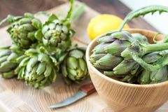 Two artichoke bouquets on kitchen table among some kitchen items.  stock photo