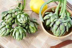 Artichoke bouquets on kitchen table. Two artichoke bouquets on kitchen table among some kitchen items. Top view royalty free stock image