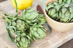 Artichoke bouquets on kitchen table. Two artichoke bouquets on kitchen table among some kitchen items. Top view stock photos