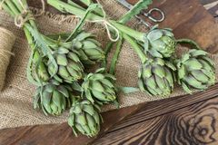 Two artichoke bouquets on kitchen table among some kitchen items.  royalty free stock image