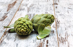 Two artichokes. Surrounded by rustic background Royalty Free Stock Image