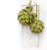 Two artichokes hanging from a vintage door Royalty Free Stock Photos
