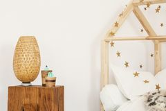 Two artificial cactuses and wicker lamp standing on wooden bedside table in white kid room interior stock photography