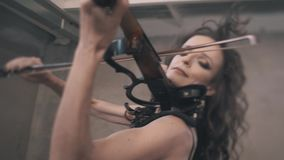 Two artistic girls, one with a violin and the other with a cello, play their instruments very emotionally and pose for the camera. Close-up in the dynamics stock video footage