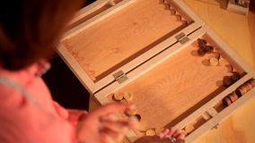 Two artistic girls play backgammon in a restaurant.  stock video
