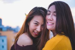 Two asia lesbian lgbt couple at roof top party in sunset evening Stock Photos